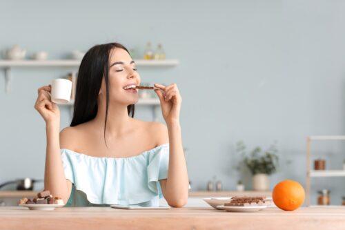 Žena sedí a chutná jedlo s kávou ochutnaj čo je koučing